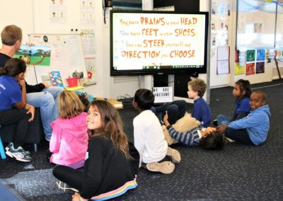 teacher holding up book while several students watch sitting down on the ground