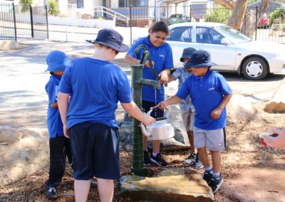 Several students around the nature play water pump