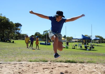 student jumping on sand